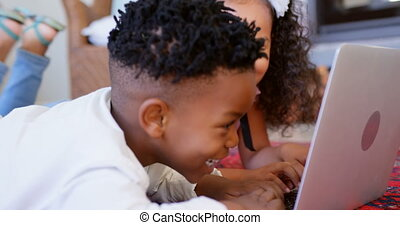 Side view of cute black siblings using laptop in living room at comfortable home 4k