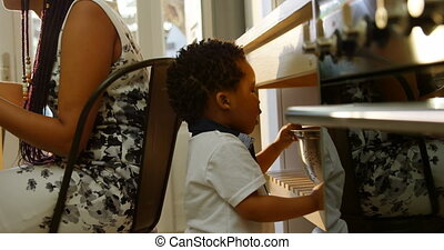 Side view of cute little black son looking in colander in kitchen of comfortable home 4k