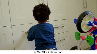 Side view of cute little black son playing in a comfortable home 4k