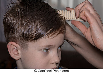 Side view of cute little boy getting haircut by hairdresser at the barbershop