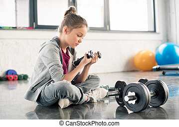 Side view of cute little girl sitting on floor and exercising with dumbbells