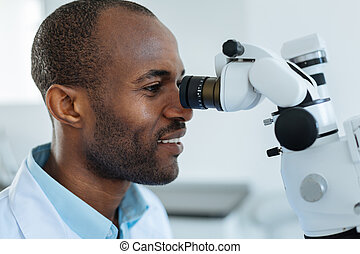 Side view of dentist looking into microscope lens