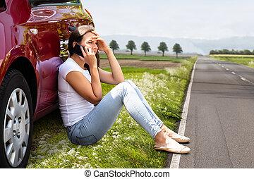 Woman Sitting On Road Near Breakdown Car