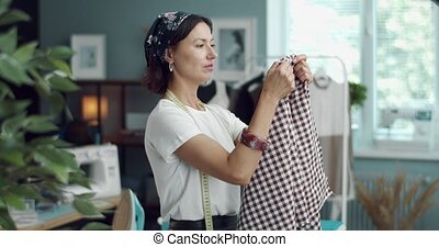 Side view of fashion designer estimating checkered fabric for new clothing collection. Mature woman with brown hair testing textile at modern studio.