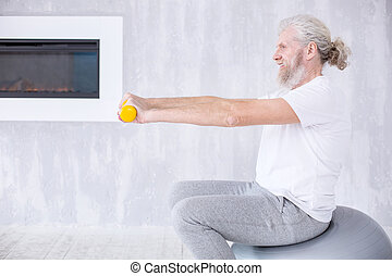 Side view of elderly man exercising with dumbbells on fitness ball