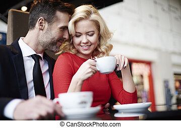 Side view of embraced couple in cafe