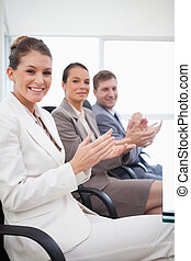 Side view of employees applauding after presentation