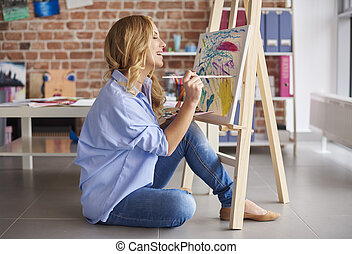 Side view of fascinated female artist