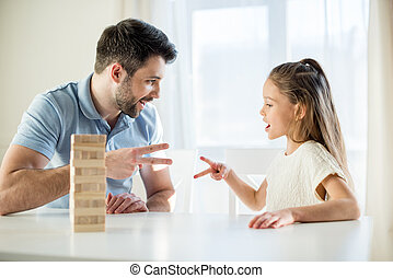 side view of father and daughter playing rock, paper, scissors game