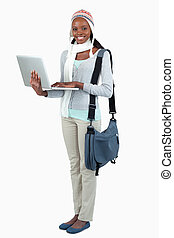 Side view of female student in winter clothing and laptop