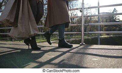 Side view of females legs walking on bridge