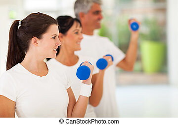 side view of fit family exercising with dumbbells