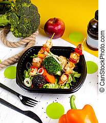 side view of fried chicken on skewers with fresh vegetables broccoli and onions in a delivery box
