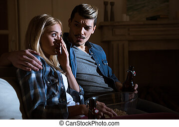 frightened woman watching movie with man