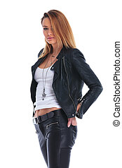 side view of girl in leather jacket posing in white studio background with hands in back pockets looking at the camera