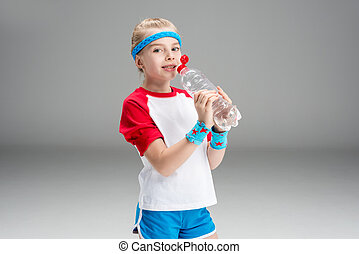 side view of girl in sportswear drinking water isolated on grey