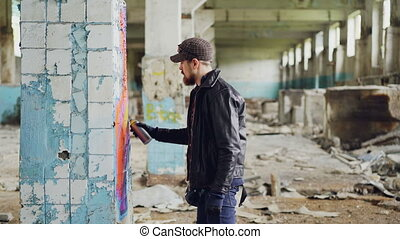 Side view of graffiti artist bearded guy drawing on damaged...