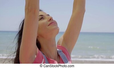 Side view of grinning woman with arms up