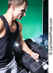 SIde view of handsome bodybuilder holding heavy dumbbell