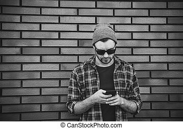 Side view of handsome young man in smart casual wear holding mobile phone while leaning at the brick wall.