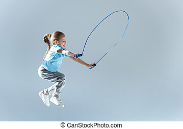 side view of happy girl humping exercising with skipping rope on grey