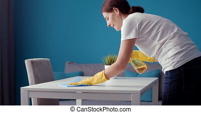 Side view of housewife in protective gloves cleaning table...