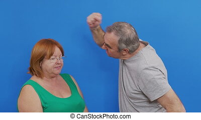 Side view of Indian couple sorting things out. Spouses quarrel, emotionally gesticulating. Man doing aggressive slap gesture. Isolated on blue background