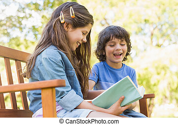 Side view of kids reading book on park bench - Side view of...