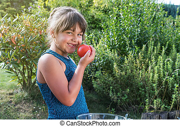 Side view of laughing little girl tasting fresh tomato