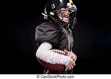 Side view of little boy american football player in uniform holding ball