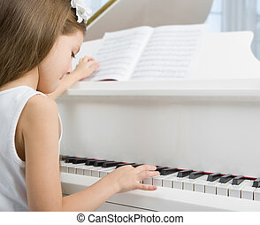 Side view of little child in white dress playing piano