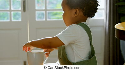 Side view of little cute black boy playing with coffee mug in living room of comfortable home 4k