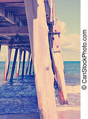 Side view of long jetty pier overlooking sandy beach with...