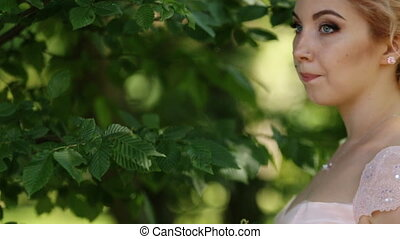 Side view of magical beautiful young blonde bride in elegant dress with bouquet roses in the park