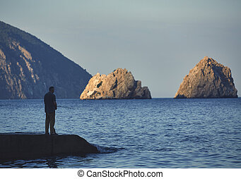 fisherman standing on a pier with a fishing rod at sunset