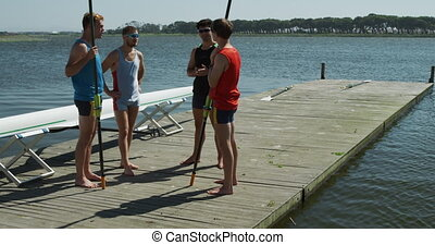 Side view of male rower discussing on the jetty - Side view ...