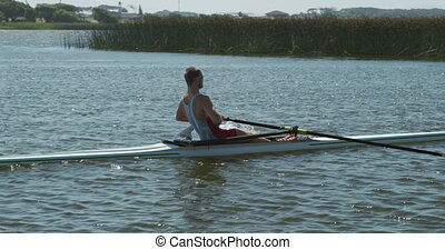 Side view of male rower practicing rowing on the lake - Side...
