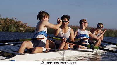 Side view of male rower team celebrating on the lake - Front...