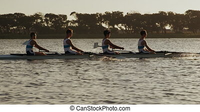 Side view of male rower team rowing on the lake - Side view ...
