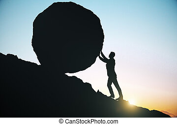 Side view of male silhouette pushing huge rock uphill. Beautiful sky background. Difficulty concept