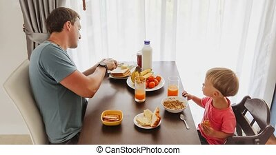 Side view of man and little boy having meal together at table in light morning time. Father and child enjoying breakfast