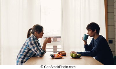 Side view of man and woman drinking tea and talking sitting at table in kitchen together enjoying peaceful morning at home. Drinks and people concept.