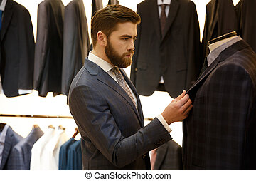 Side view of man choosing a jacket in shop - Side view of...