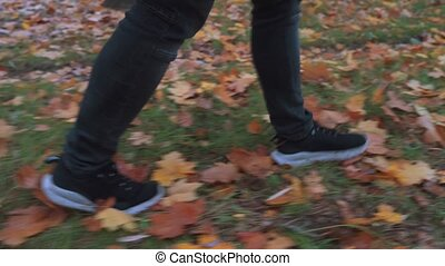 Side view of Man in sneakers and black skinny jeans kicking ...