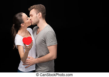 Side view of man kissing woman with heart in hand on black
