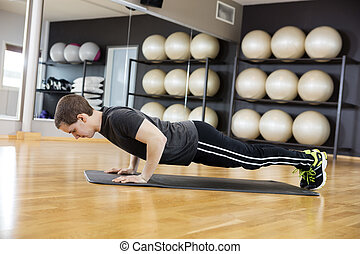 Side View Of Man Performing Pushups In Gym