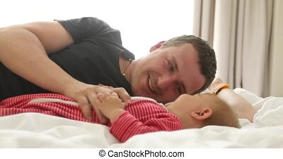 Side view of man playing with his little baby