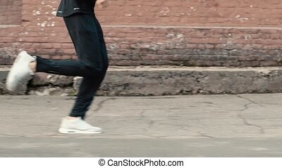 Side view of man running fast along old street. Slow motion...
