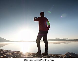 Side View of Man Taking Selfie Photos at the Beach. Hot morning Sun rising over lake.