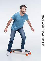 side view of man trying to ride skateboard on white